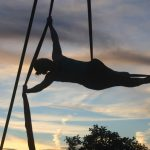 An aerial silks artist is silhouetted against the sunset in Madison